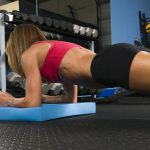 Fit woman lying on the floor doing planks, for triceps and full body strengthening and balance.